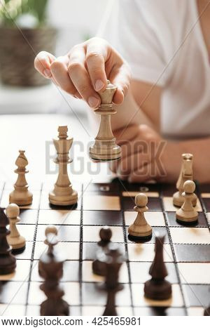 Close-up Of A Childs Hand With A Chess Piece In Hand. Queen Move. Chess Games And Learning For Child