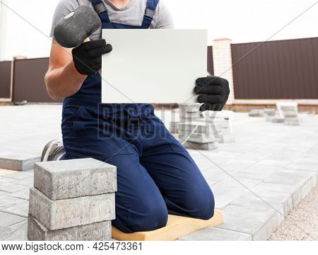 bricklayer holding the white sheet of paper in hand with gloves.  mockup for house repair or building