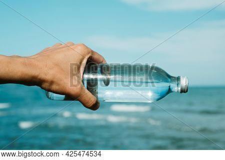 closeup of a young caucasian man holding a glass reusable bottle with water in his hand, in front of the ocean, aligned with the horizon
