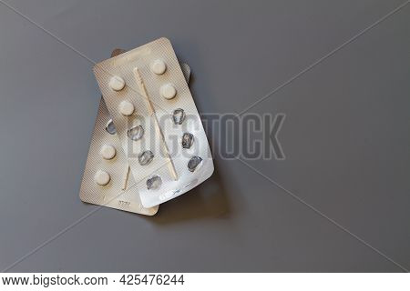 White Tablets In A Foil Blister On A Gray Background, Several Tablets Eaten. Copy Space.