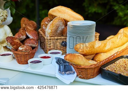 Bread And Stack Of Plates For Group Catering.