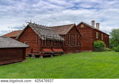 Idyllic Red Cottages In The Swedish Countryside With Green Meadows On A Beautiful Summer Day