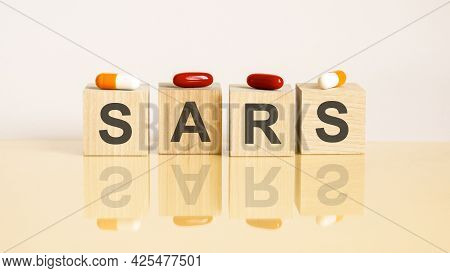 Word Sars Is Made Of Wooden Cubes On A Yellow Background With Pills