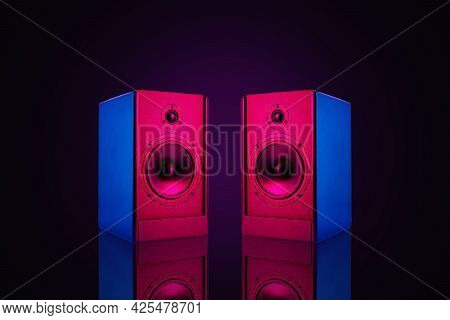 Two Neon Colored Stereo Speakers On Dark Background With Reflection.sound Audio Loud Speakers, Close