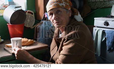 80s Wrinkled Woman Having Breakfast And Looking Into Camera With Misunderstanding Face. Portrait Of