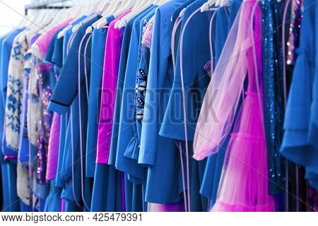 Women's Clothing Boutique With Colorful Dresses On Hangers. Blue Pink And Lilac Dresses Close Up. Ba