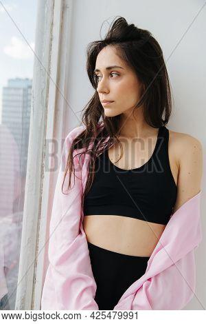 Dreamy Armenian Woman In Black Top And White Shirt Looking Away Near Window