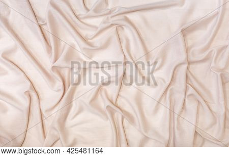 Abstract Background From A Beautiful Beige Fabric Draped With Soft Folds.