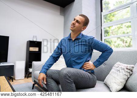 Man Sitting On Sofa Having Back Pain