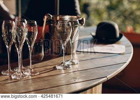 Several Empty Beautiful Glass Wine Glasses Stand On The Table With Glare From The Sun.