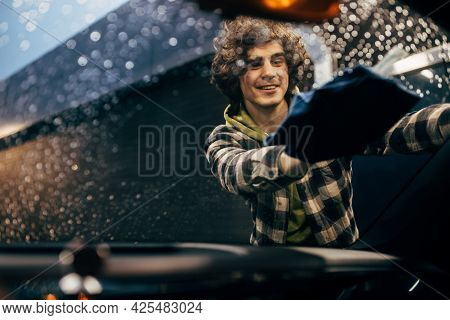 Smiling Driver Cleaning Windshield Of Car With Rag In Evening