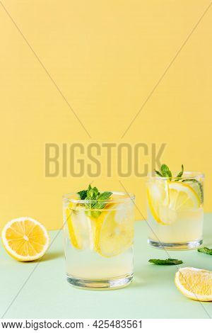 Two Glasses Of Ice Lemon Water With Mint Leaves On A Yellow And Green Background. Fresh Summer Drink
