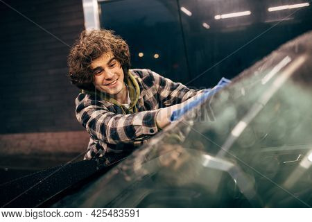Young Driver Cleaning Windshield With Rag On Self Service Car Wash