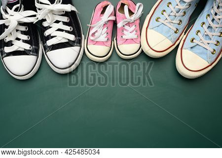 Many Multi-colored Well-worn Textile Sneakers Of Different Sizes On A Green Background, Top View, Co