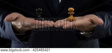 Business Planning Strategy And Concept. A Businessman In A Dark Suit Holds White And Black Chess Paw