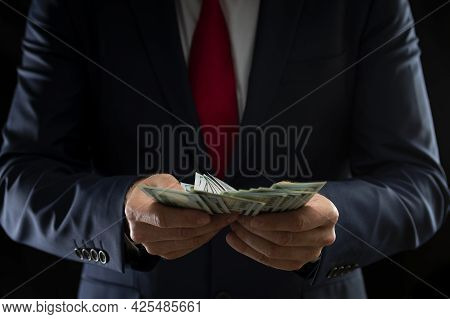 Businessman Holding American Dollars In His Hands