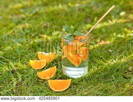 Drinking Glass With Orange Slices And Water On The Grass. Cold Lemonade Drink With Orange And Mint I