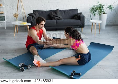 Fit Young Couple Holding Hands And Stretching Legs On Fitness Mats At Home