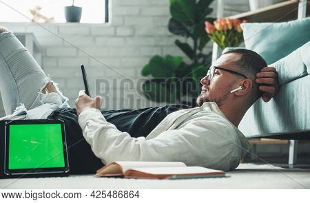 Caucasian Man Working On A Tablet With Free Space Is Lying On The Floor Near The Couch Chatting On M