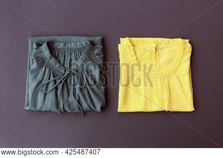 Two Womens Blouses Of Yellow And Gray Colors Are Neatly Folded, Top View