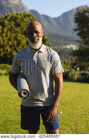 Portrait of smiling senior african american man with yoga mat in stunning countryside. retirement and active senior lifestyle concept.