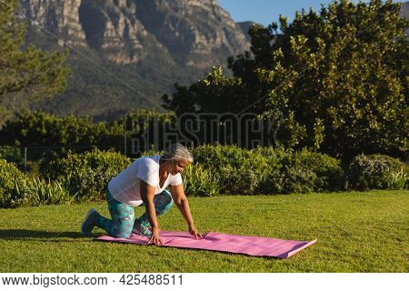 Senior african american woman kneeling on yoga mat on grass in stunning countryside. retirement and active senior lifestyle concept.