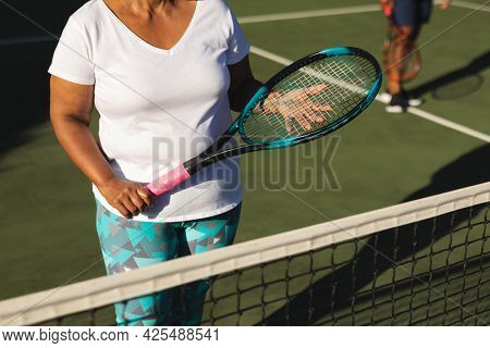 Midsection of senior african american woman holding tennis racket on tennis court. retirement and active senior lifestyle concept.