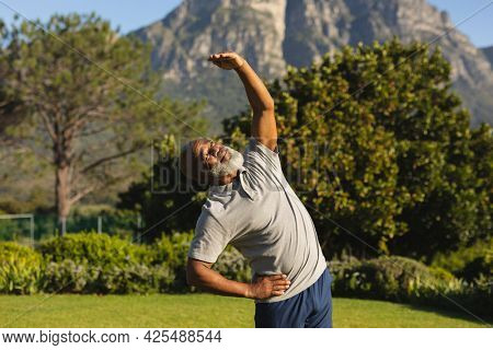 Senior african american man exercising outdoors in stunning countryside. retirement retreat and active senior lifestyle concept.