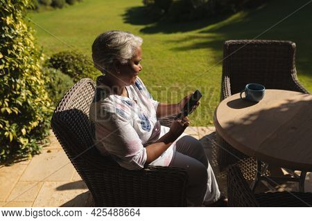 Senior african american woman using smartphone in sunny garden. retreat, retirement and happy senior lifestyle concept.