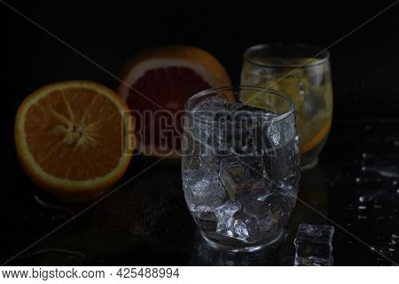 Cooking Lemonade Water In A Glass Of Ice And Fruit Orange Grapefruit On A Black Background. Summer D
