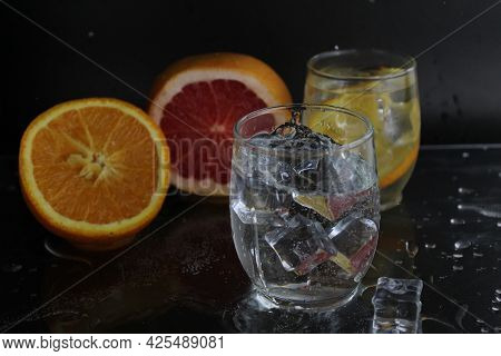 Splashes Of Water Over A Glass Of Water And Ice. Nearby Are Fruits Orange And Grapefruit, Ice. On A