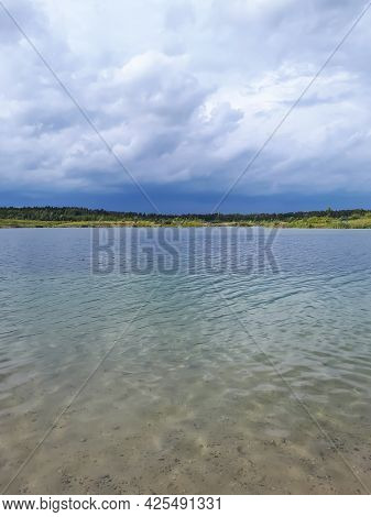 Landscape Of Lake And Forest In The Far And Texture Of Crystal Clear Light Blue, Green And Turquoise