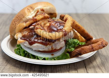 Barbeque Chicken Sandwich Stacked Tall In The Toasted Bun With Huge Onion Rings On The Side To Fill