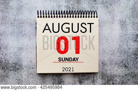 First Of August On Wall Calendar In Bright Sunlight. Number One In Red Rectangle With Shadow.