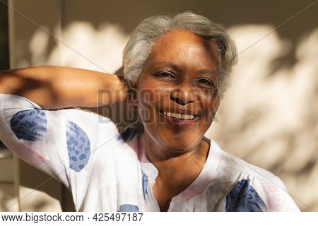 Portrait of smiling senior african american woman on shaded terrace. retreat, retirement and happy senior lifestyle concept.