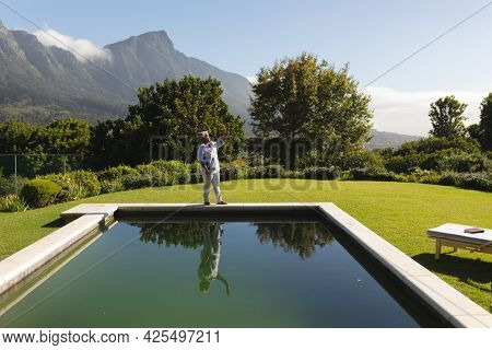 Senior african american woman taking smartphone selfie by swimming pool in sunny garden. retreat, retirement and happy senior lifestyle concept.