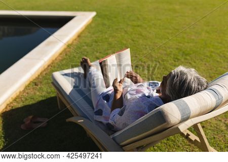 Senior african american woman reading book in deckchair by swimming pool in sunny garden. retreat, retirement and happy senior lifestyle concept.