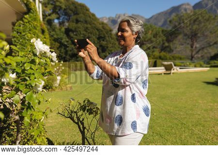 Senior african american woman taking photos with smartphone in sunny garden. retreat, retirement and happy senior lifestyle concept.