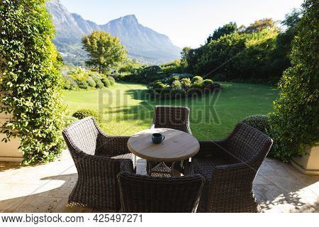 General view of table and wicker chairs on terrace with stunning mountains countryside view. outdoor retreat and holiday concept.
