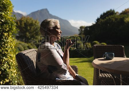 Senior african american woman talking on smartphone in sunny garden. retreat, retirement and happy senior lifestyle concept.