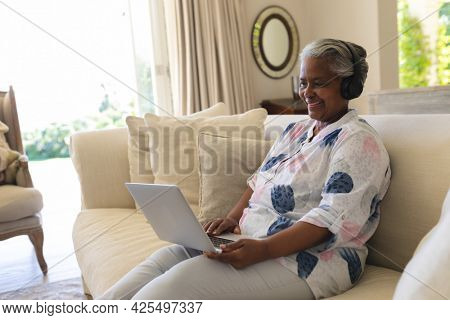 Senior african american woman sitting on sofa wearing headphones using laptop. retreat, retirement and happy senior lifestyle concept.
