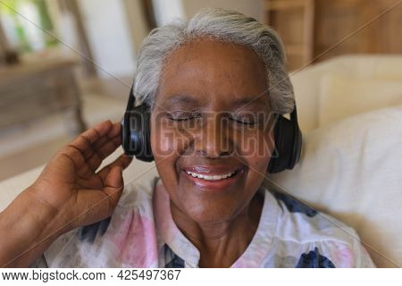 Senior african american woman sitting on sofa wearing headphones with eyes closed. retreat, retirement and happy senior lifestyle concept.
