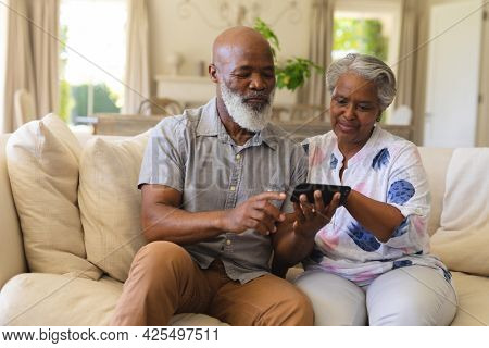 Senior african american couple sitting on sofa using smartphone. retreat, retirement and happy senior lifestyle concept.