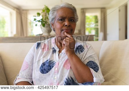 Portrait of senior african american woman sitting on sofa looking at camera. retreat, retirement and happy senior lifestyle concept.