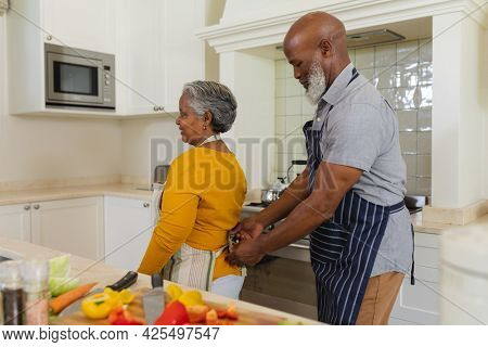 Senior african american couple cooking together in kitchen smiling. retreat, retirement and happy senior lifestyle concept.