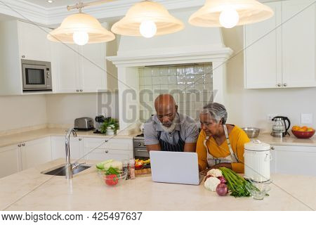 Senior african american couple cooking together in kitchen using laptop. retreat, retirement and happy senior lifestyle concept.