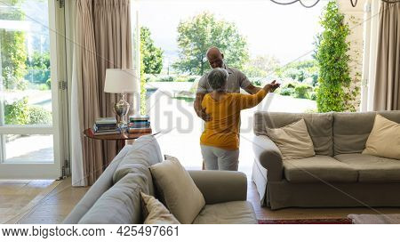 Senior african american couple dancing together in living room. retreat, retirement and happy senior lifestyle concept.