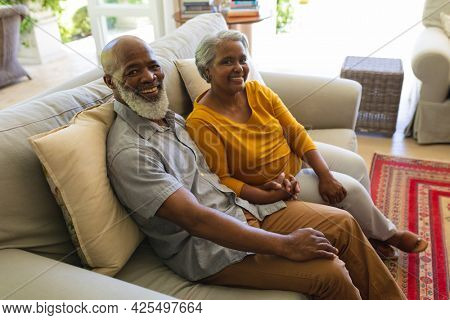 Portrait of senior african american couple sitting on sofa holding hands looking at camera smiling. retreat, retirement and happy senior lifestyle concept.