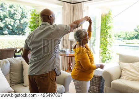 Senior african american couple dancing together in living room smiling. retreat, retirement and happy senior lifestyle concept.