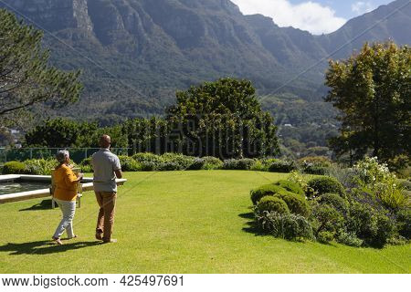 Senior african american couple spending time in sunny garden together drinking coffee. retreat, retirement and happy senior lifestyle concept.